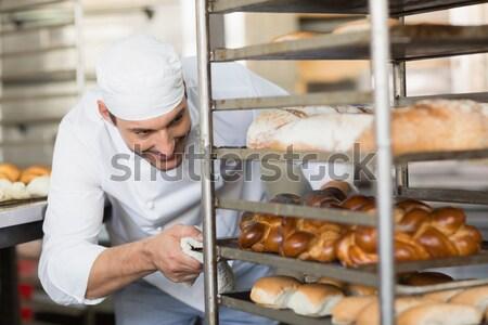 Sorridere guardando vassoio pane cucina panetteria Foto d'archivio © wavebreak_media