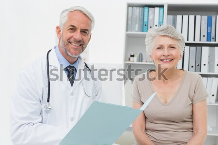 Patient showing thumbs up sign while standing with doctor Stock photo © wavebreak_media