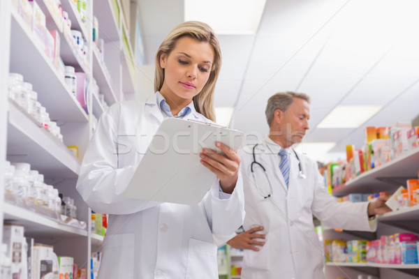 Young trainee writing on a prescription pad Stock photo © wavebreak_media