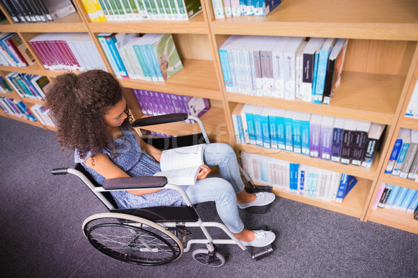Smiling disabled student in library reading book Stock photo © wavebreak_media