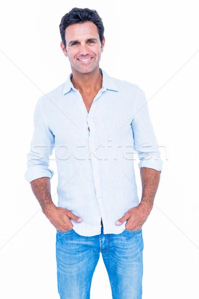счастливым красивый мужчина глядя камеры рук кармана Сток-фото © wavebreak_media