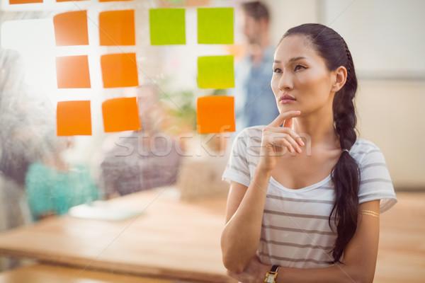 Concentrado empresária olhando postar parede escritório Foto stock © wavebreak_media