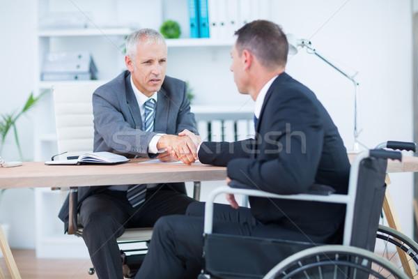 Businessman in wheelchair shaking hands with colleague Stock photo © wavebreak_media