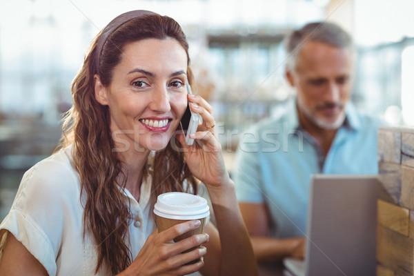 Pretty brunette smiling at camera and having phone call Stock photo © wavebreak_media