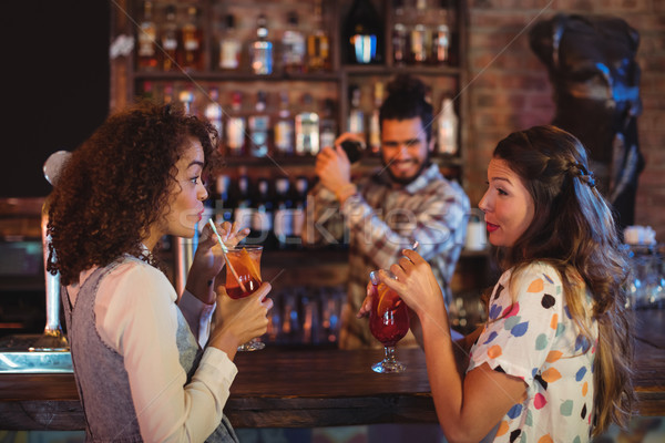 Two young women having cocktail drinks at counter Stock photo © wavebreak_media