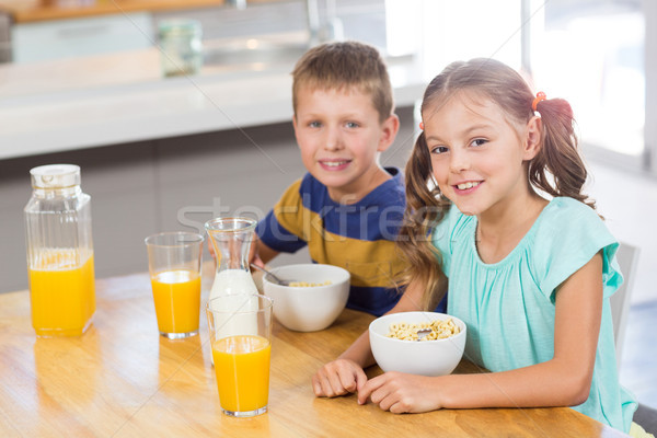Portrait of smiling sibling having breakfast cereal in kitchen Stock photo © wavebreak_media