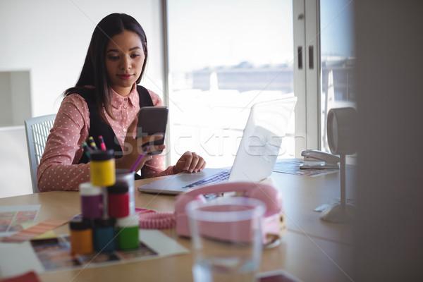 Jovem empresária telefone móvel mesa de escritório criador negócio Foto stock © wavebreak_media
