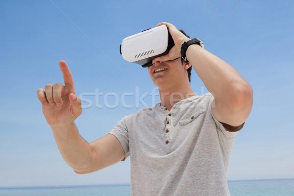 Man using vr headset against the blue sky Stock photo © wavebreak_media