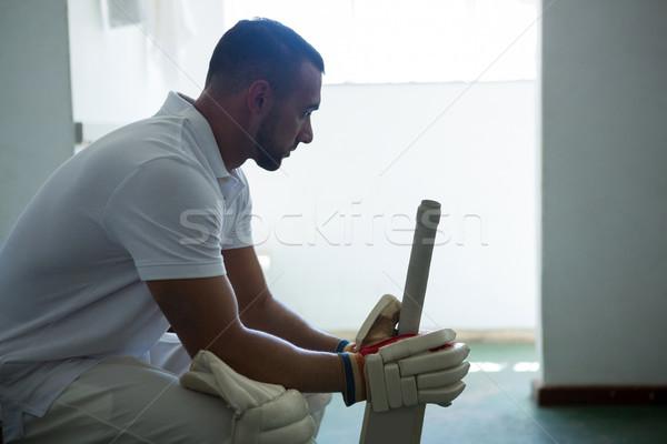 Vue de côté cricket joueur séance banc vestiaire Photo stock © wavebreak_media
