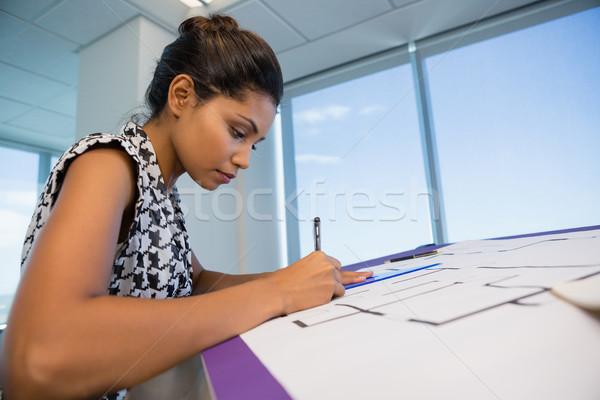 Female architect working on blueprint Stock photo © wavebreak_media