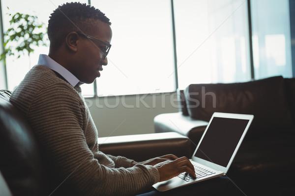Uważny wykonawczej za pomocą laptopa biuro komputera telefonu Zdjęcia stock © wavebreak_media