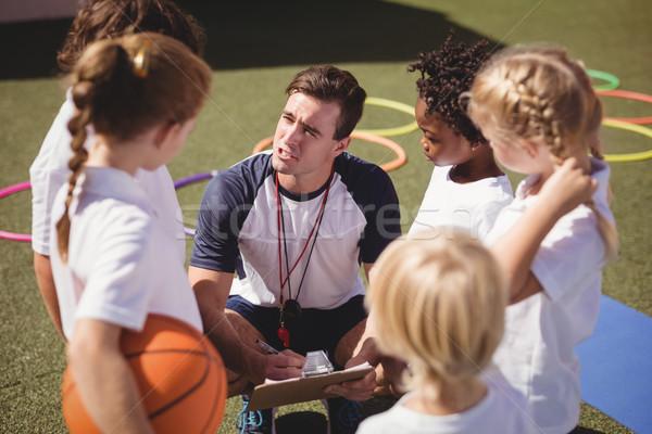 Edző iskolás gyerekek megbeszél vágólap lány férfi Stock fotó © wavebreak_media