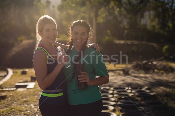 Portrait of happy friends holding water bottle during obstacle course Stock photo © wavebreak_media