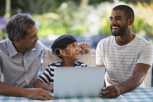 Szczęśliwy rodziny posiedzenia laptop weranda tabeli Zdjęcia stock © wavebreak_media