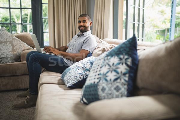 Portrait of man using laptop while sitting at home Stock photo © wavebreak_media