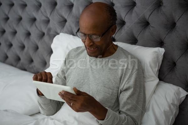 Smiling senior man using digital tablet while resting on bed Stock photo © wavebreak_media