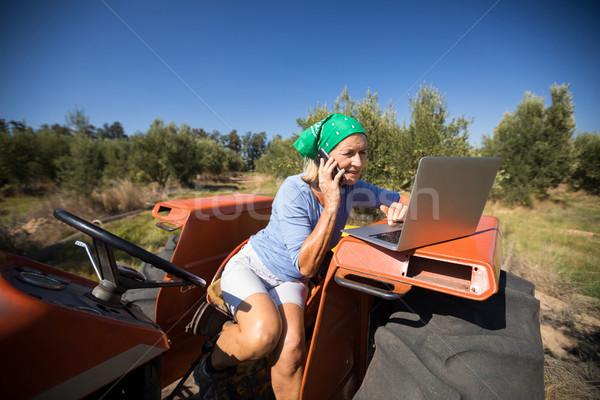 Woman using laptop while talking on mobile phone Stock photo © wavebreak_media