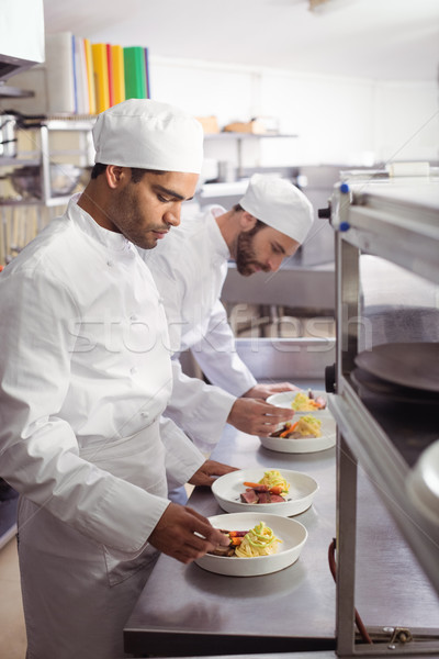 Two chefs garnishing food in commercial kitchen Stock photo © wavebreak_media