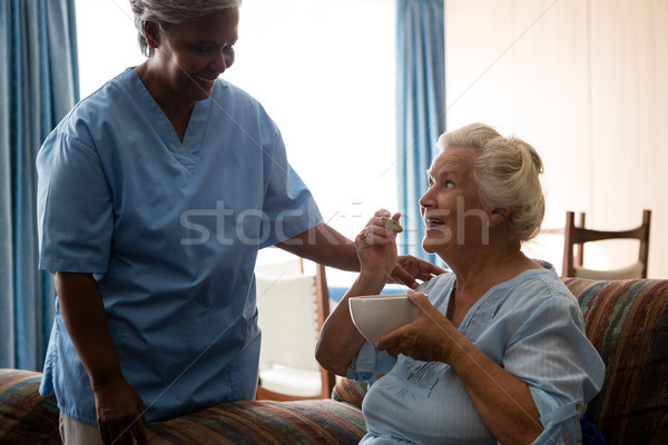 Senior woman talking to nurse while having food Stock photo © wavebreak_media