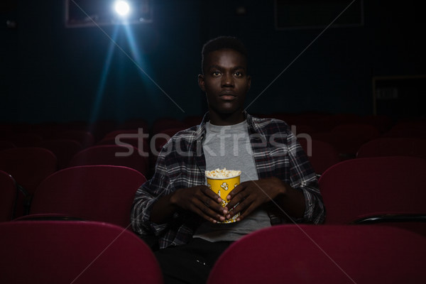Concentré homme popcorn regarder film théâtre Photo stock © wavebreak_media