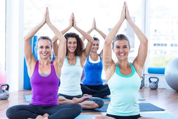 Cheerful women sitting with hands overhead in fitness studio Stock photo © wavebreak_media