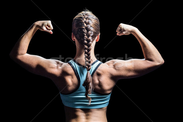 Rear view of woman with braided hair flexing muscles Stock photo © wavebreak_media