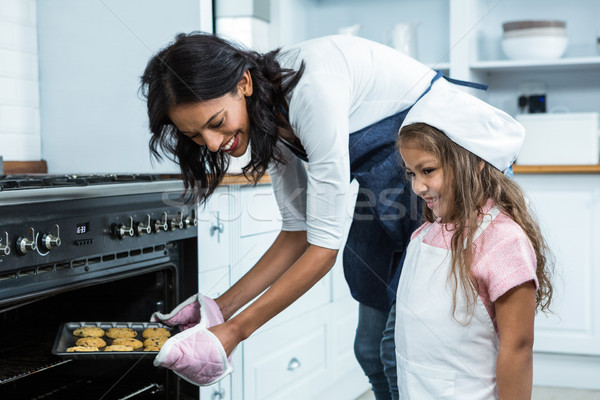 Smiling mother putting biscuits into the oven with daughter Stock photo © wavebreak_media