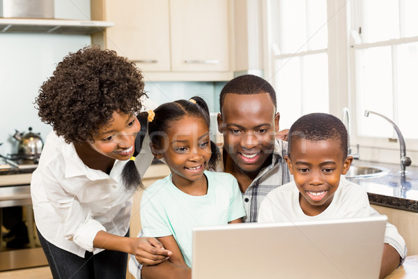 Stock photo: Happy family using laptop in the kitchen