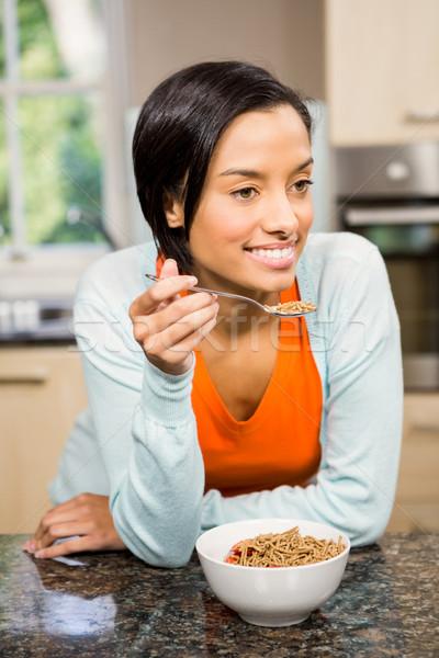 Stock photo: Smiling brunette eating cereals