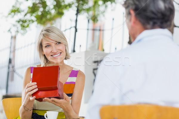 Frau halten vorliegenden schauen Mann Sitzung Stock foto © wavebreak_media