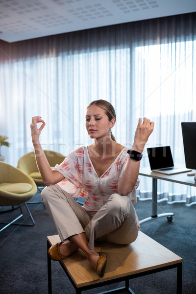 Businesswoman doing yoga with hands in the air Stock photo © wavebreak_media