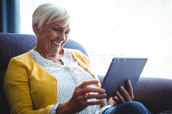 Smiling senior woman looking and laughing at her digital tablet Stock photo © wavebreak_media