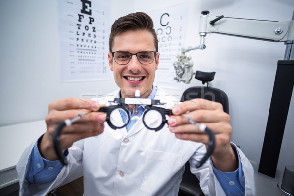 Smiling optometrist holding messbrille Stock photo © wavebreak_media