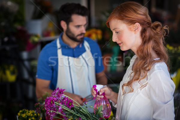 Woman spraying water on bunch of flowers while man preparing flower bouquet Stock photo © wavebreak_media