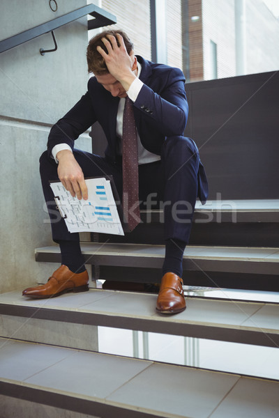 Depressed businessman with clipboard sitting on stairs Stock photo © wavebreak_media
