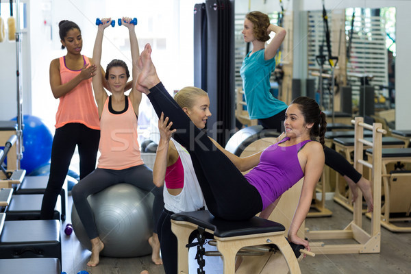 Female trainer assisting woman with stretching exercise on reformer Stock photo © wavebreak_media