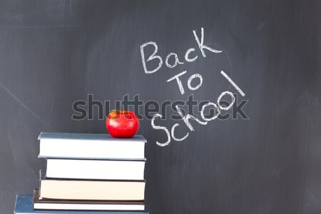 Slate with chalks by lunch bag and books on wooden table against white background Stock photo © wavebreak_media
