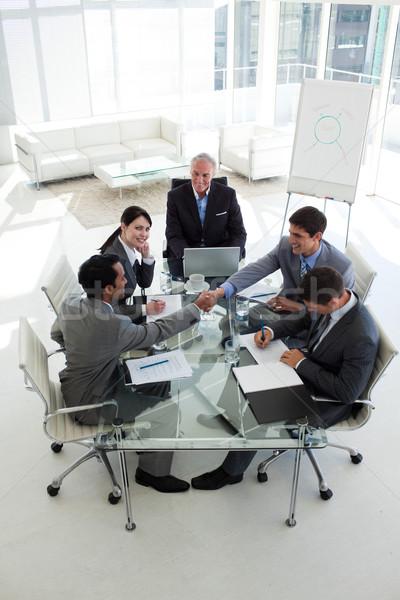 Empresarios apretón de manos sesión alrededor conferencia mesa Foto stock © wavebreak_media