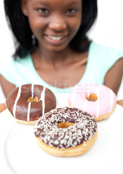 Stock photo: Smiling young woman looking at donuts