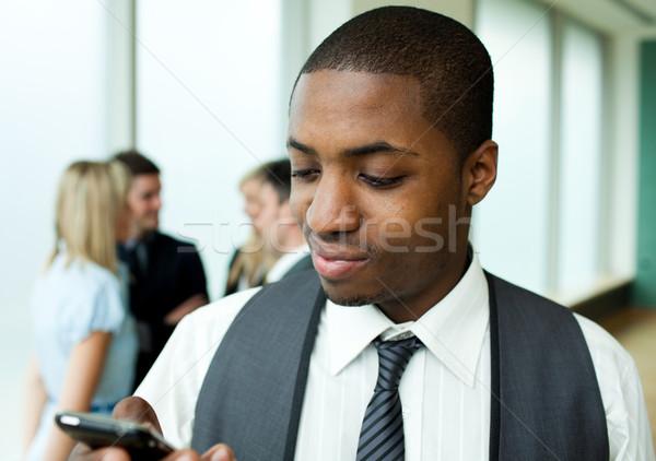 Afro-American businessman texting in office Stock photo © wavebreak_media