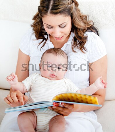 Attentive mother reading a book to her adorable baby sitting in the couch in the living-room Stock photo © wavebreak_media