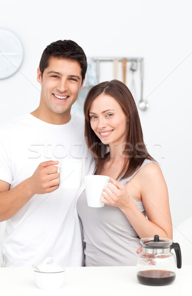 Stock photo: Portrait of a couple drinking coffee during breakfast standing in the kitchen