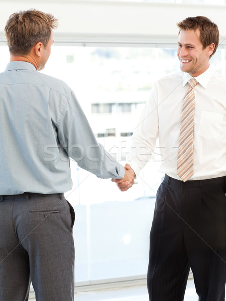 Two happy businessmen concluding a deal by shaking their hands standing in the office Stock photo © wavebreak_media
