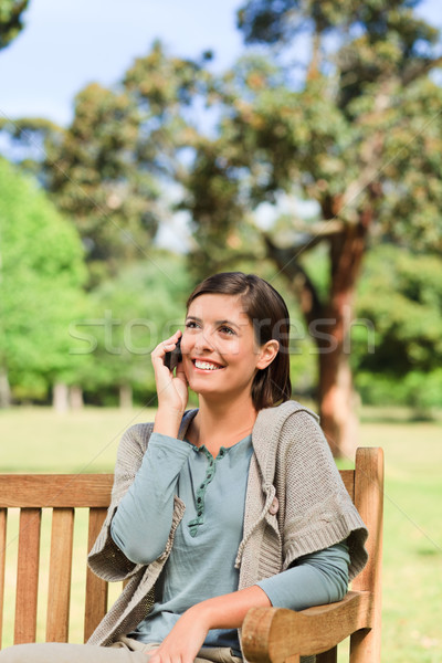 Young woman phoning on the bench Stock photo © wavebreak_media
