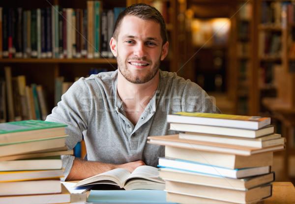 Souriant étudiant livres bibliothèque livre travaux Photo stock © wavebreak_media