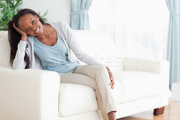 Smiling woman enjoys sitting on the couch Stock photo © wavebreak_media