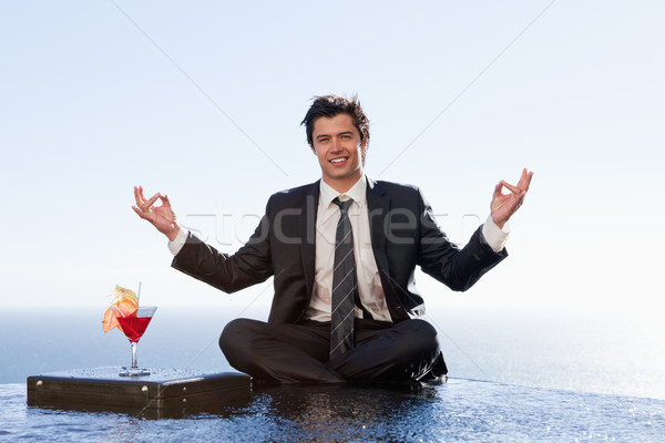 Smiling businessman relaxing in the lotus position with a cocktail in a swimming pool Stock photo © wavebreak_media