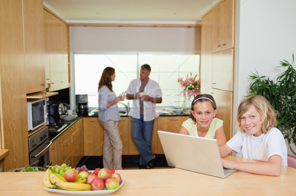 Children with their notebook in the kitchen and parents behind them Stock photo © wavebreak_media