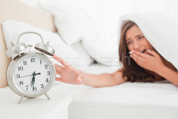 A woman is reaching out to silence her alarm clock while underneath her blanket in bed. Stock photo © wavebreak_media
