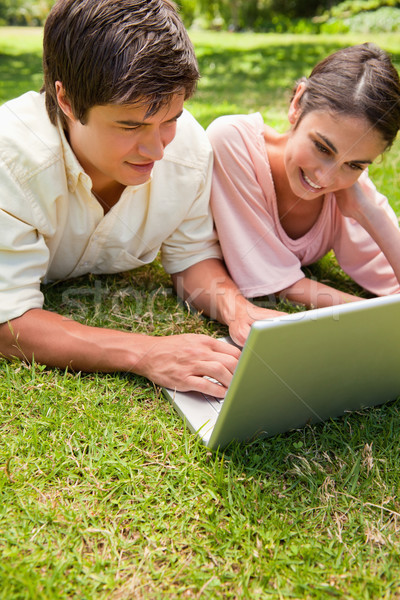 Two friends smiling as they use a laptop together while lying down on the grass Stock photo © wavebreak_media